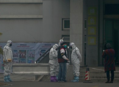 Staff in biohazard suits hold a metal stretcher by the in-patient department of Wuhan Medical Treatment Centre