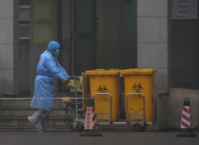Staff move bio-waste containers past the entrance of the Wuhan Medical Treatment Center