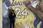 A man pays respects at a mural of Kobe Bryant in downtown Los Angeles