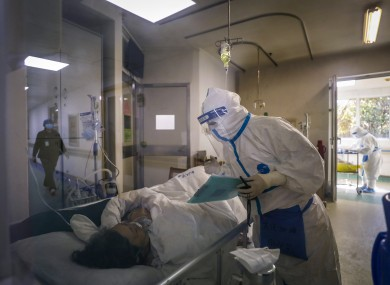 A medical worker checks on a patient at Jinyintan hospital in Wuhan.