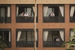 People stand on their balconies of the H10 Costa Adeje Palace hotel in the Canary Island of Tenerife