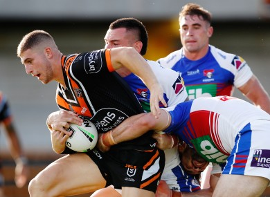 Adam Doueihi of the Tigers is tackled by the Knights defence yesterday.