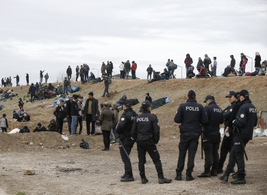 Turkish police stand by people camping in Edirne near the Turkish-Greek border.