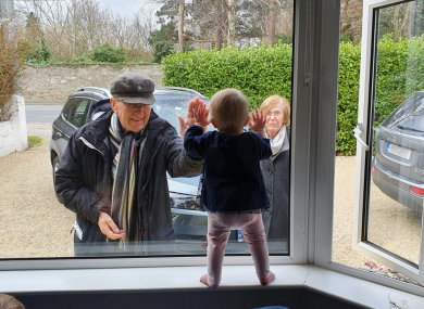 Sadhbh O'Brien greets her grandparents Ken and Maeve Whitaker through the front window of her home in Dublin.