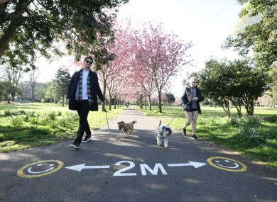 Tim Moylan and Aisling Healy practise social distancing while walking their dogs Lucy and Ellie in Herbert Park Dublin on 11 April.