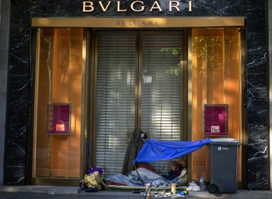 A man rests at the gate of a luxury shop in downtown Barcelona