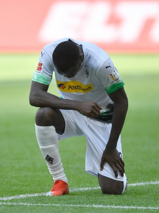 Mönchengladbach's Marcus Thuram kneels on the grass after his opening goal.