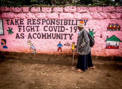 A woman walks past a wall with graffiti raising awareness about Covid-19 in Kenya.