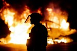 A police officer stands near a car burning in Austin, Texas.