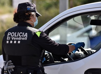 A police officer wearing a surgical mask verifies the identification of a driver at a mobility checkpoint to ensure compliance with the rules of confinement.