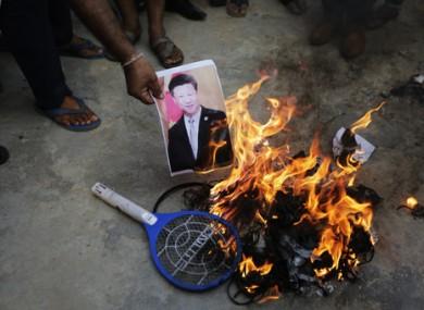 An Indian man burns a photograph of Chinese president Xi Jinping.
