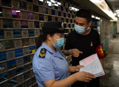 A supervisor examines the stock records of food and other products at the Yuegezhuang wholesale market in Beijing