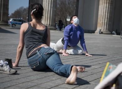 Masked-up yogis at the Brandenburg Gate in Berlin