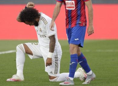 Real Madrid's Marcelo kneels as he celebrates his goal.