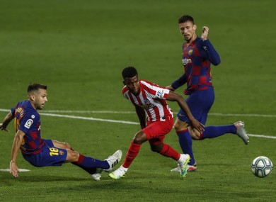Atletico Madrid's Thomas Lemar, center, fights for the ball next to Barcelona's Jordi Alba, left, and Barcelona's Clement Lenglet, right.