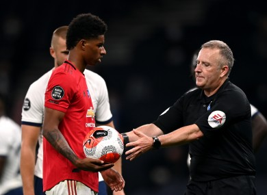 Jon Moss takes the ball from Marcus Rashford after United's second penalty was overturned by VAR late on.
