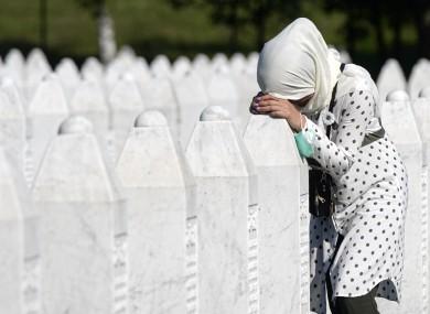 A woman by a grave stone in Potocari, near Srebrenica, Bosnia today.