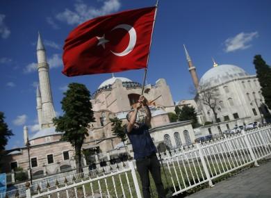 A man waves a Turkish flag outside the Byzantine-era Hagia Sophia.