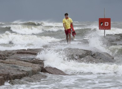 A lifeguard walks along a rock groin in Galveston, Texas, as waves kicked up by tropical storm Hanna wash in