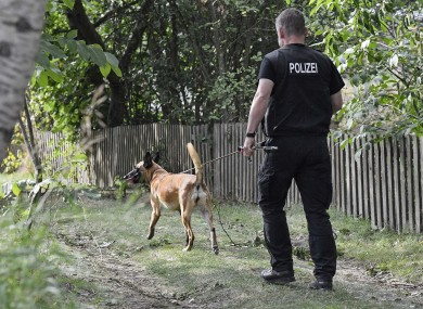 A German police officer walks with a search dog during an investigating at an allotment garden plot in Seelze, near Hannover
