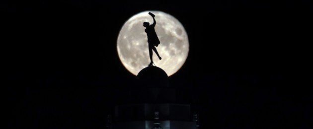 The full moon rises over a dancing lady on the Spanish city building in Whitley Bay.