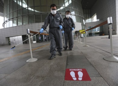 Workers spray disinfectant as a precaution against a new coronavirus at the National Museum of Korea in Seoul, South Korea