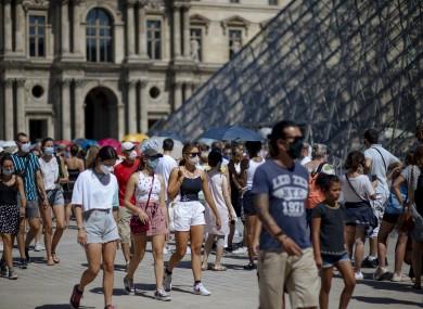 People walk past the Louvre Museum in Paris earlier this week.