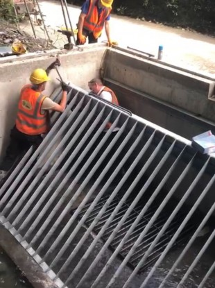 Council workers installing the trash screen.