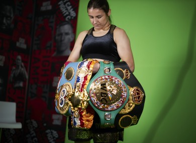 Katie Taylor glances at the belts that make her the undisputed lightweight champion of the world.