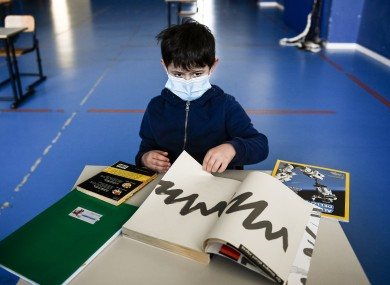 A child sits in a makeshift classroom inside a gym, as part of a pilot test to see how schools can reopen after Covid-19 in the region of Piedmont, Italy.