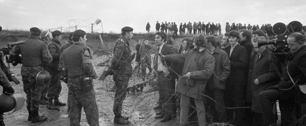 John Hume, wearing a white shirt and addressing an army officer, is one of the two Stormont MPs who accused the army of brutality towards marchers in an anti-internment demonstration.