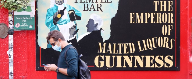 A man wearing a face mask passing The Temple Bar pub in Dublin city centre yesterday.