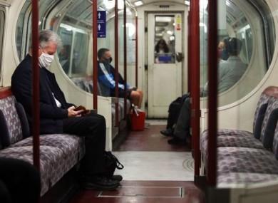 Commuters in London wear face masks.