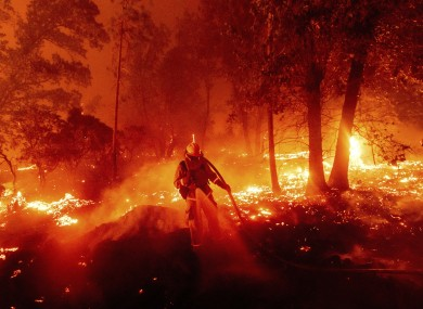 A firefighter battles the Creek Fire as it threatens homes in California.