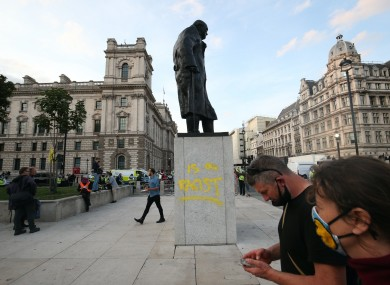 """The statue of Winston Churchill, after it was vandalised with the words """"Is a racist"""" sprayed in yellow paint on the plinth, in Parliament Square"""
