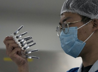 An employee manually inspects syringes of the SARS CoV-2 Vaccine