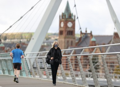 A woman walks across the Peace Bridge over the River Foyle in Derry.