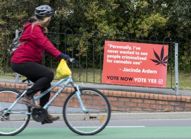 A Christchurch cyclist rides past a sign in support of making marijuana legal