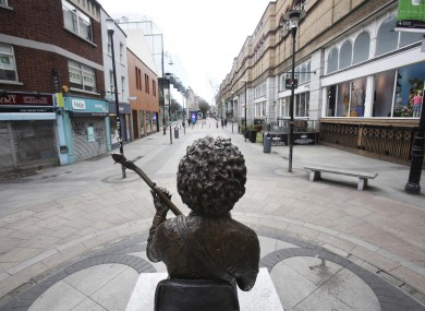 A statue of Luke Kelly looks down towards an empty Kings Street, Dublin.