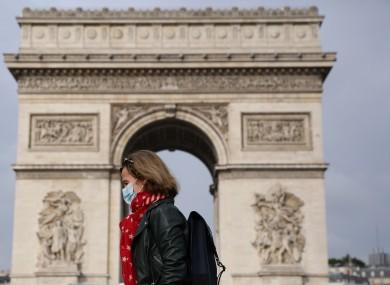 A woman walks past the Arc de Triomphe in Paris