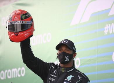 Lewis Hamilton holds aloft a Michael Schumacher helmet after winning yesterday's Eifel Grand Prix.