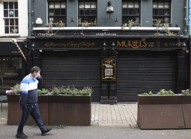 A man wearing a face mask walks past a closed pub in Belfast