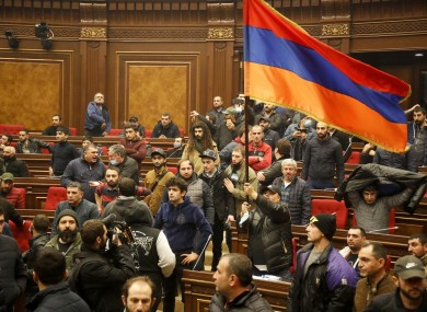 Demonstrators with an Armenian national flag protest against an agreement to halt fighting over the Nagorno-Karabakh region, at the parliamentary building in Yerevan, Armenia