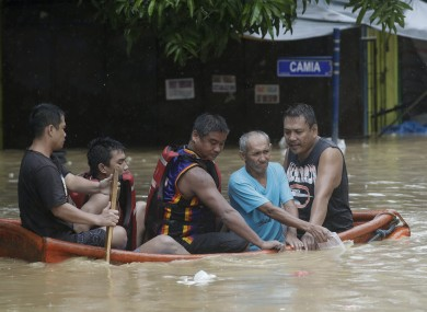 Residents ride a boat as they evacuate from their flooded homes in Marikina, Philippines