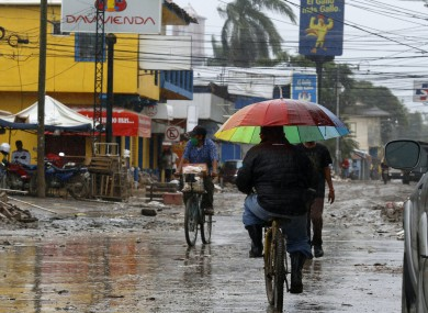 Locals move on street barely cleared from the debris of the last storm, before Hurricane Iota makes landfall in La Lima, Honduras