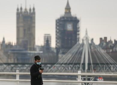 A man walking along the Waterloo Bridge in London today.