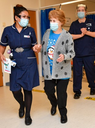 Margaret Keenan, 90, walks with nurse May Parsons after receiving the vaccine.