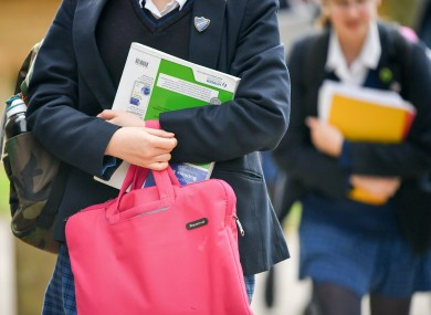 File image of student holding bag and books.