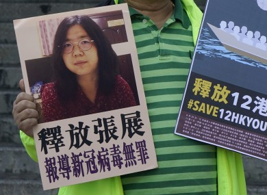A pro-democracy activist holds placards with the picture of Chinese citizen journalist Zhang Zhan outside the Chinese central government's liaison office, in Hong Kong