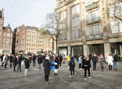 People wait to enter a shop near Dam square in Amsterdam.